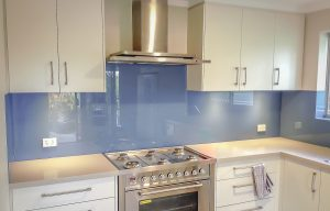 Kitchen glass splashbacks in blue metallic coloured glass