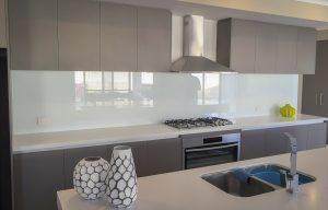 Grey kitchen with white splashbacks and Benchtops