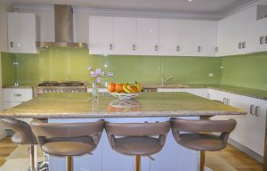 Modern kitchen with green painted glass splashbacks